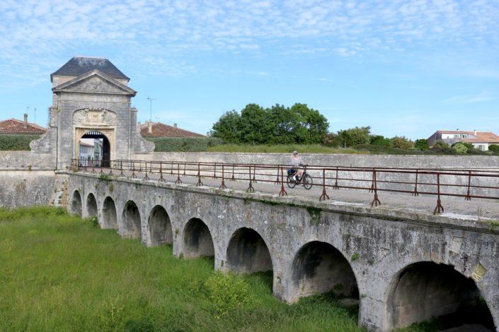 À vélo devant la porte des Campani à Saint-Martin-de-Ré